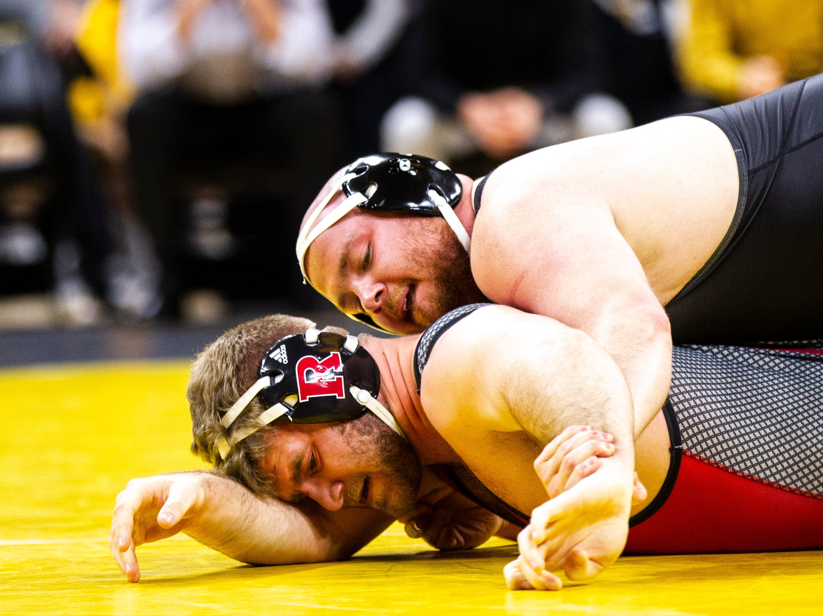 Iowa's Sam Stoll, top, wrestles Rutgers' Christian Colucci at 285 during a NCAA Big Ten Conference wrestling dual on Friday, Jan. 18, 2019, at Carver-Hawkeye Arena in Iowa City, Iowa.