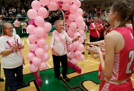 Cancer survivor Sharon Coffey, 83, left, walks under the ballon arch during the 11th annual Pink Out game at Triton Central High School onFriday, Jan. 18, 2019. The Pink Out game honors breast cancer survivors and supports the I.W.I.N. (Indiana Women in Need). Foundation.