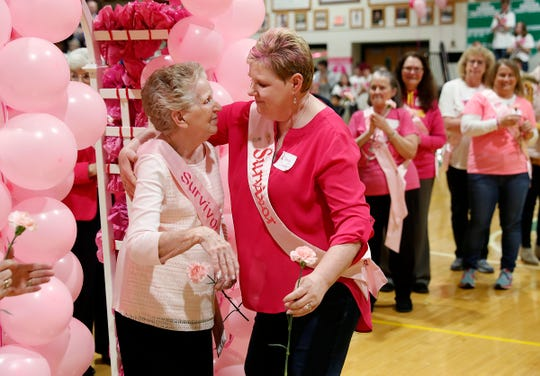 Sharon Coffey, 83, left, hugs her daughter and fellow cancer survivor Nancy Cossairt,55, right, during the 11th annual Pink Out game at Triton Central High School onFriday, Jan. 18, 2019. The Pink Out game honors breast cancer survivors and supports the I.W.I.N. (Indiana Women in Need). Foundation.