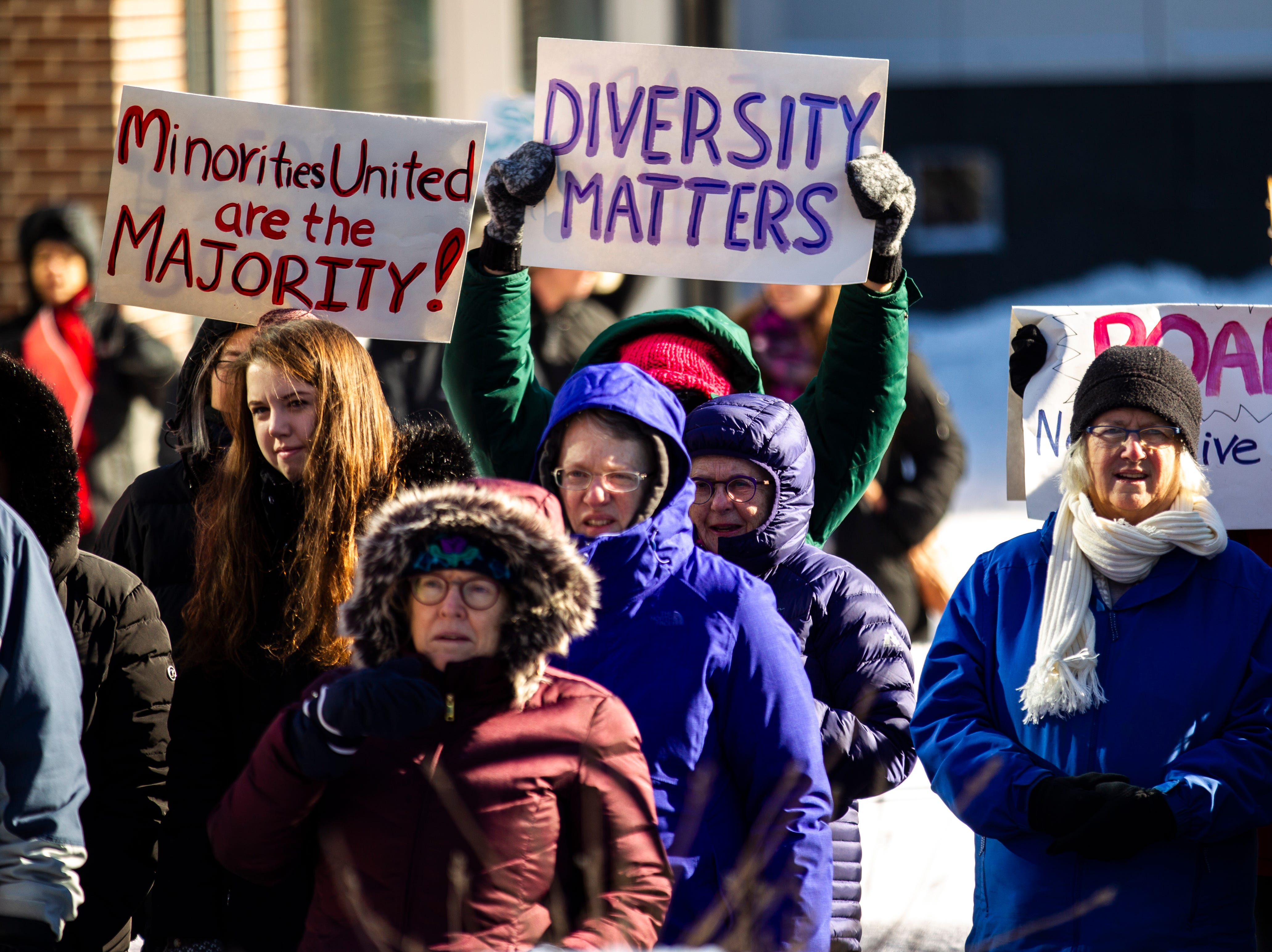 "Community members gather while holding up signs reading, ""Minorities united, are the majority!"" and ""Diversity matters"" during the ""Women's March"" on Saturday, Jan. 19, 2019, along the pedestrian mall in downtown Iowa City, Iowa."