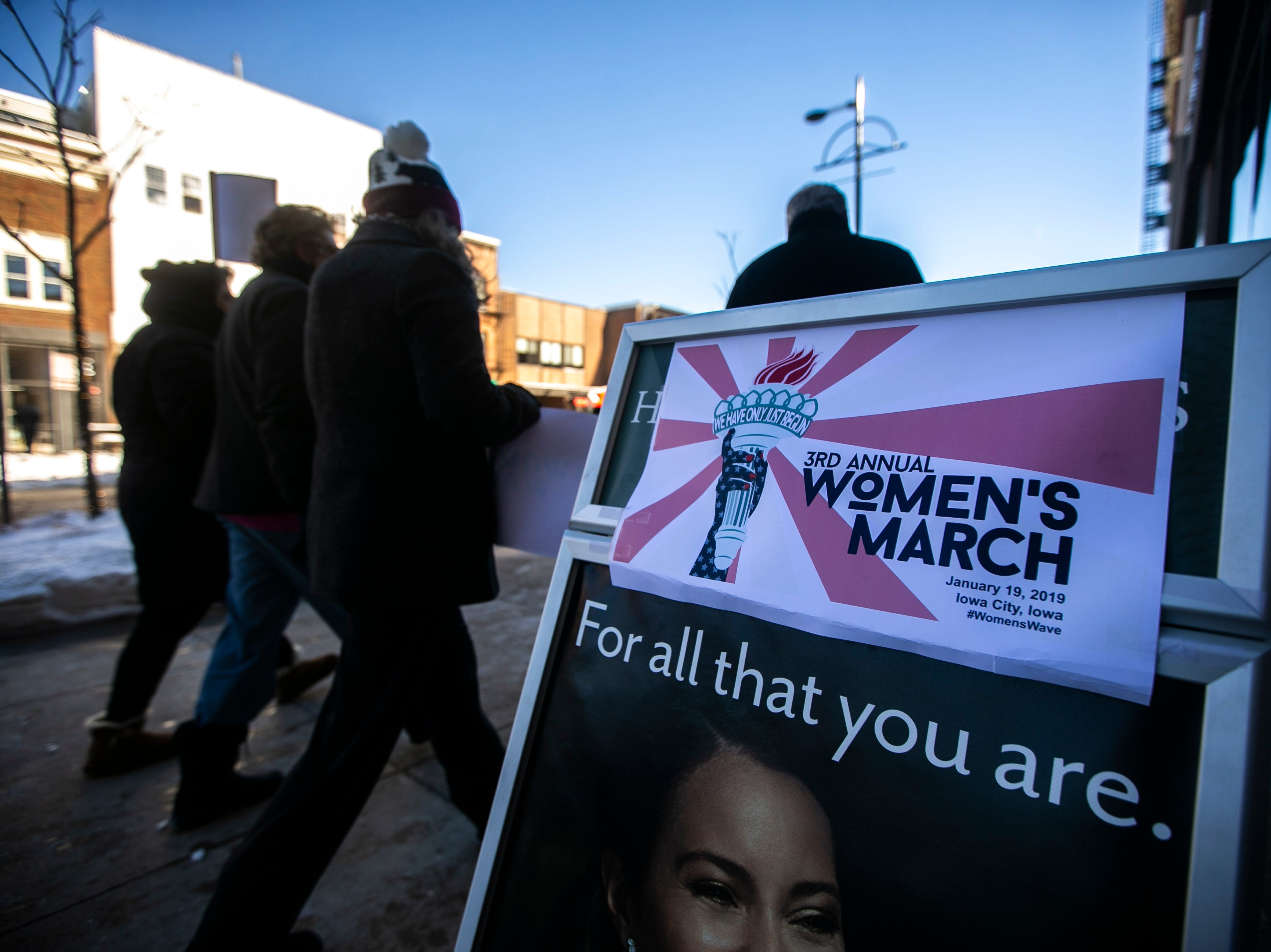 "Community members walk past a sign for the event attached to an image of a woman that reads, ""For all that you are."" during the ""Women's March"" on Saturday, Jan. 19, 2019, along the pedestrian mall in downtown Iowa City, Iowa."
