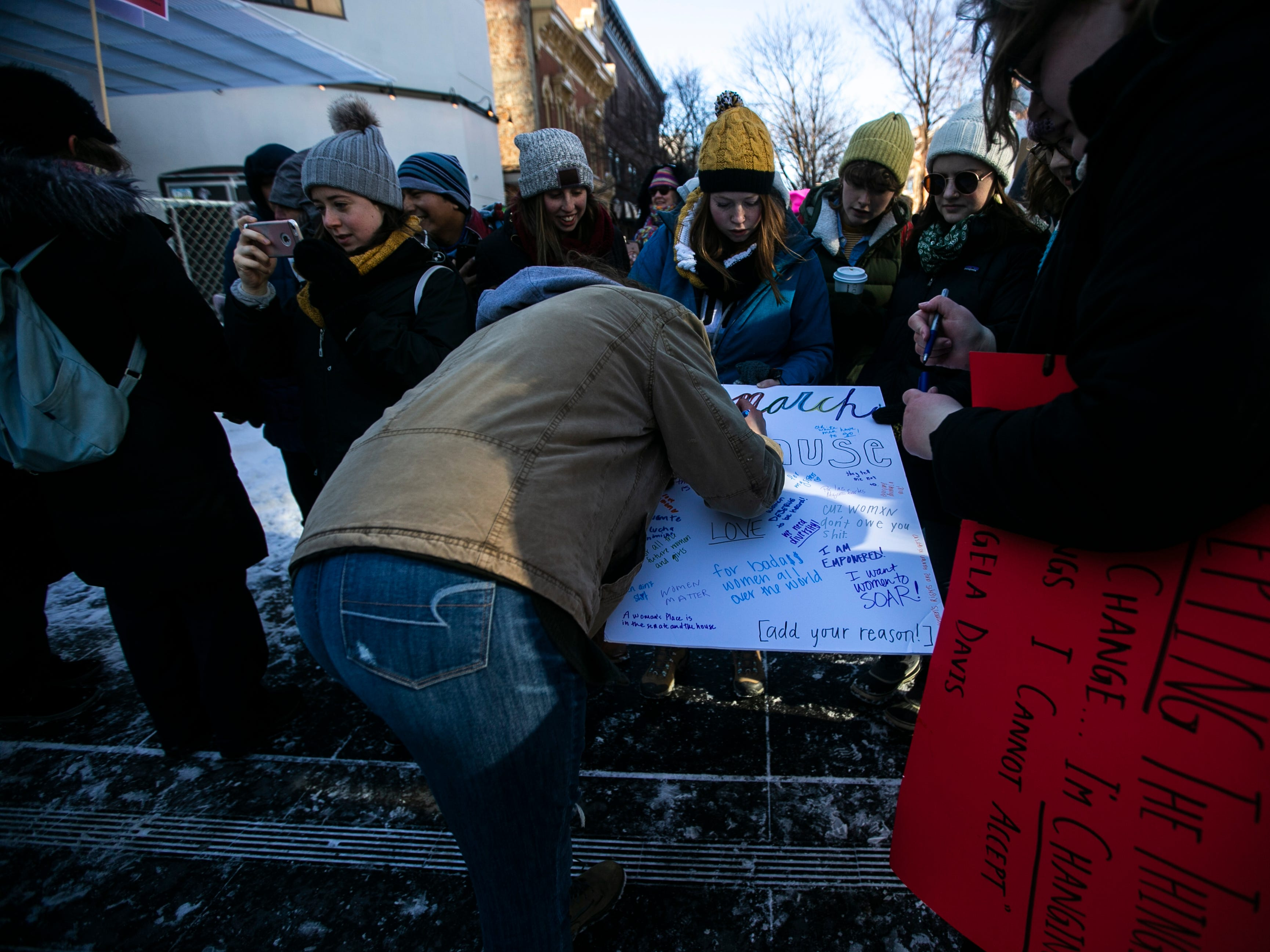 "A group of women hold a sign while they encourage community members to write the reason why the attended the protest following the ""Women's March"" on Saturday, Jan. 19, 2019, along the pedestrian mall in downtown Iowa City, Iowa."