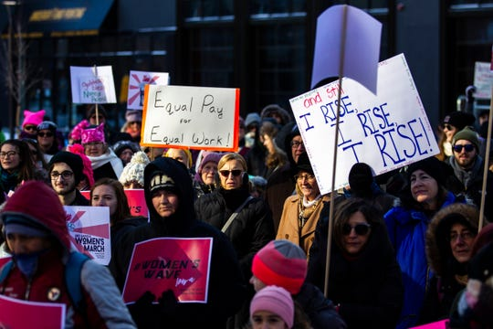 """Community members gather while holding up signs readings, """"Equal pay for equal work!"""" and """"...and still I rise, I rise, I rise!"""" during the """"Women's March"""" on Saturday, Jan. 19, 2019, along the pedestrian mall in downtown Iowa City, Iowa."""
