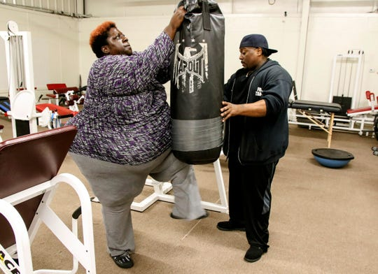 Leneathra Reed, left, works with her trainer, Frank Harbin, at Total Body Transformation Gym in Meridian, Miss., on Friday, Jan. 4, 2019. Since sharing her story on social media, Reed, 39, has become a viral sensation, inspiring others to drop a few pounds. Finding time to exercise is a challenge for the single mother and full-time student at the University of Phoenix. But Reed, who also works full time and is active in her church, said that if she can make the time, then others can find their way to their gym.