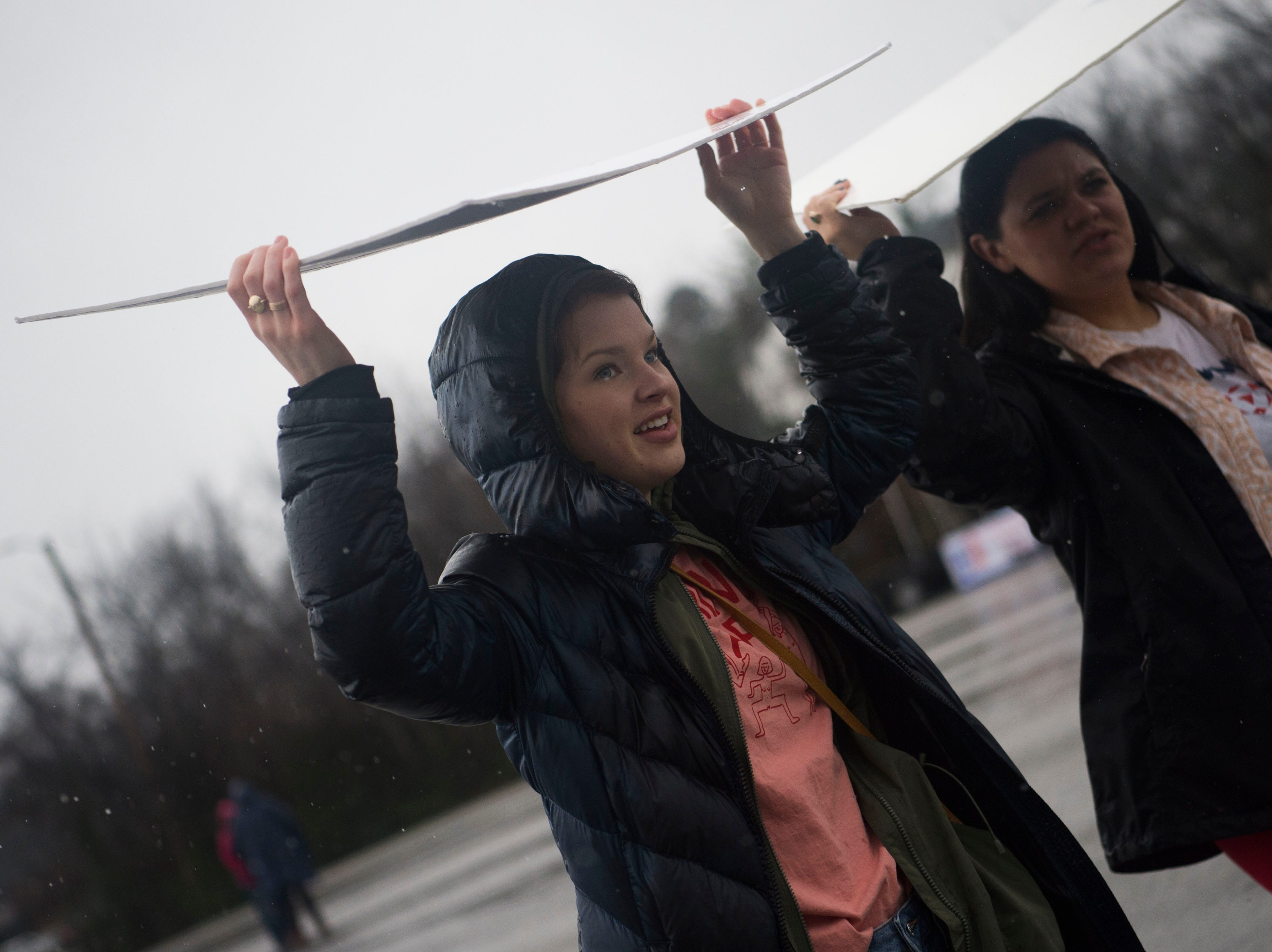 From left University of Tennessee students Martha Higgs and Jayne Garbar stay dry under their signs during the 2019 Women's March in Chilhowee Park Saturday, Jan. 19, 2019.