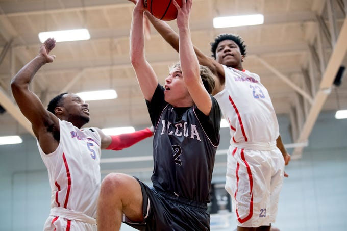 Alcoa's Garrett Rogers (2) goes for a point as Austin-East's Ronney Pierson (5) and LaRon Dixon (23) defend during a game between Austin-East and Alcoa at Austin-East High School in Knoxville, Tennessee on Friday, January 18, 2019.