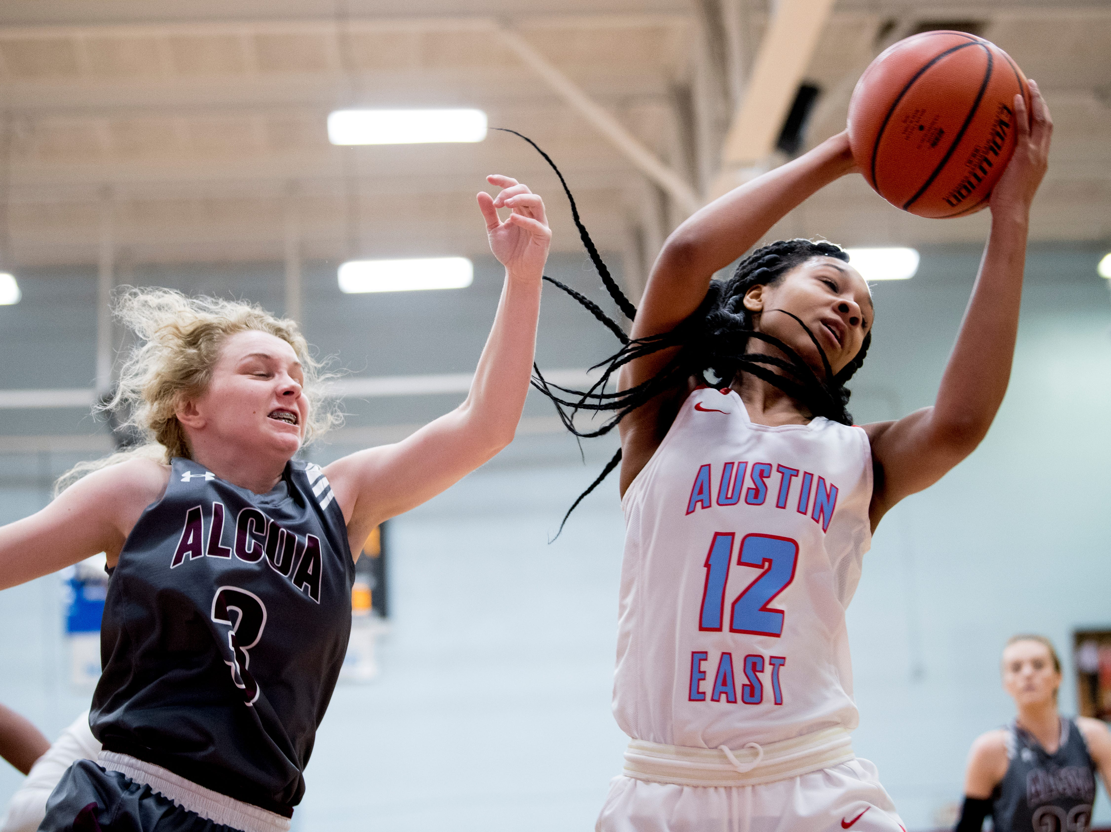 Austin-East's Trinity Turner (12) grabs the ball as Alcoa's Dee Dee Shodery (3) tries to defend during a game between Austin-East and Alcoa at Austin-East High School in Knoxville, Tennessee on Friday, January 18, 2019.