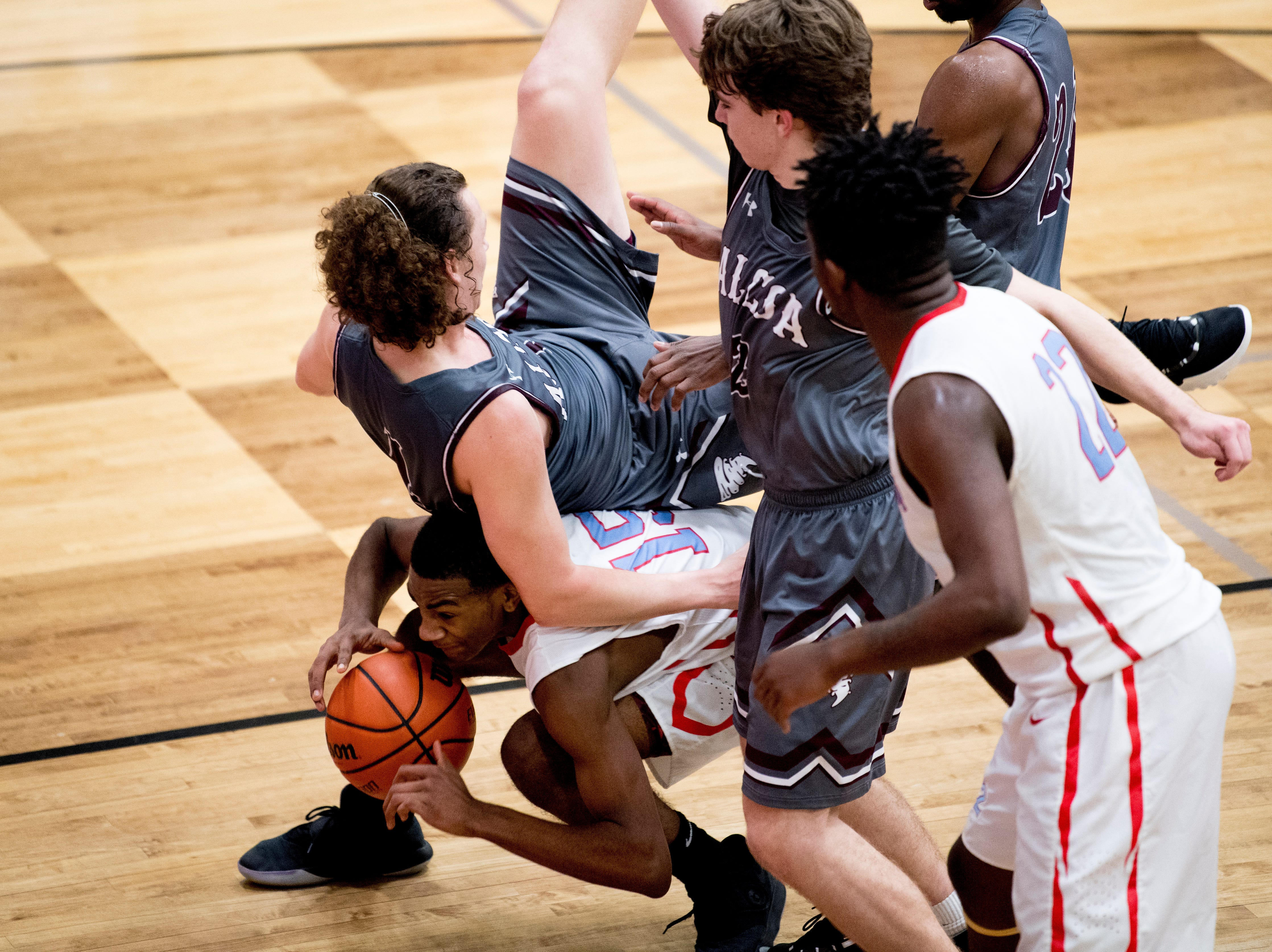 Alcoa's Nick Roberts (4) falls atop Austin-East's Ka'Juan Bullard (15) during a game between Austin-East and Alcoa at Austin-East High School in Knoxville, Tennessee on Friday, January 18, 2019.