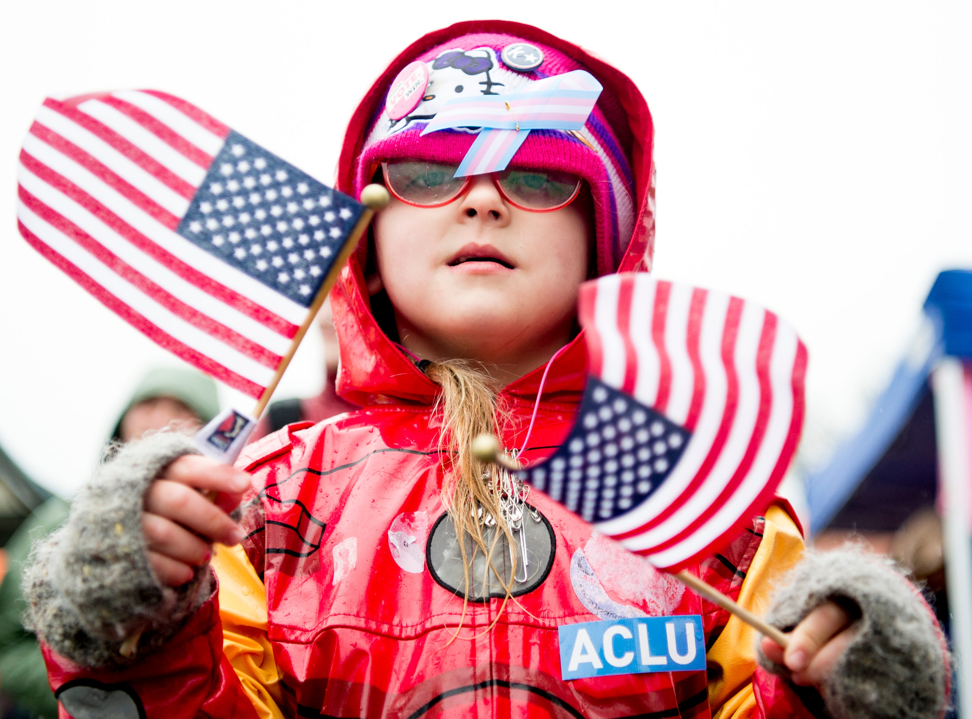 A young demonstrator waves American flags at the 2019 Knoxville Women's March at Chilhowee Park in Knoxville, Tennessee on Saturday, January 19, 2019.