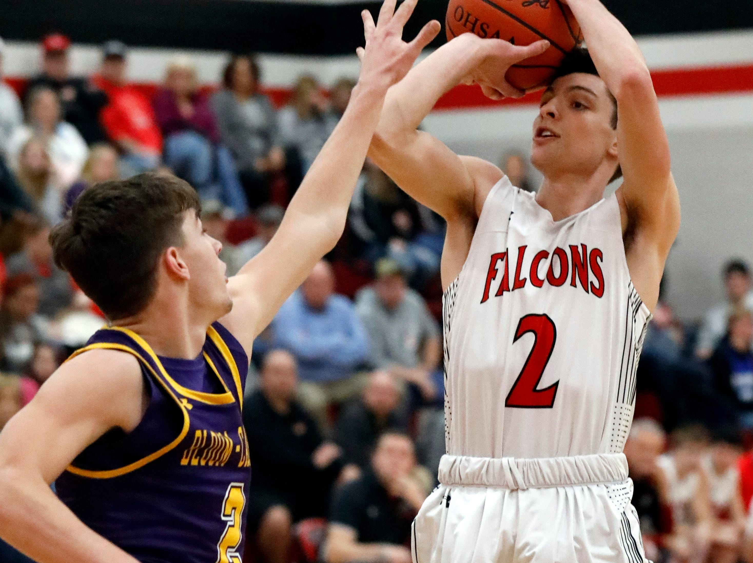 Fairfield Union's Evan Conley takes a shot over Bloom-Carroll's Otto Kuhns during Friday night's game, Jan. 18, 2019, at Fairfield Union High School in Rushville. The Falcons defeated the Bulldogs 42-31.