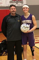 Fowlerville senior Elie Smith was presented a commemorative basketball by coach Billy Selvia for scoring her 1,000th career point.