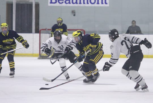 Hartland's Adam Pietila (10) controls the puck between Plymouth's Gavin Roach, left, and Nicholas Schoen on Friday, Jan. 18, 2019.