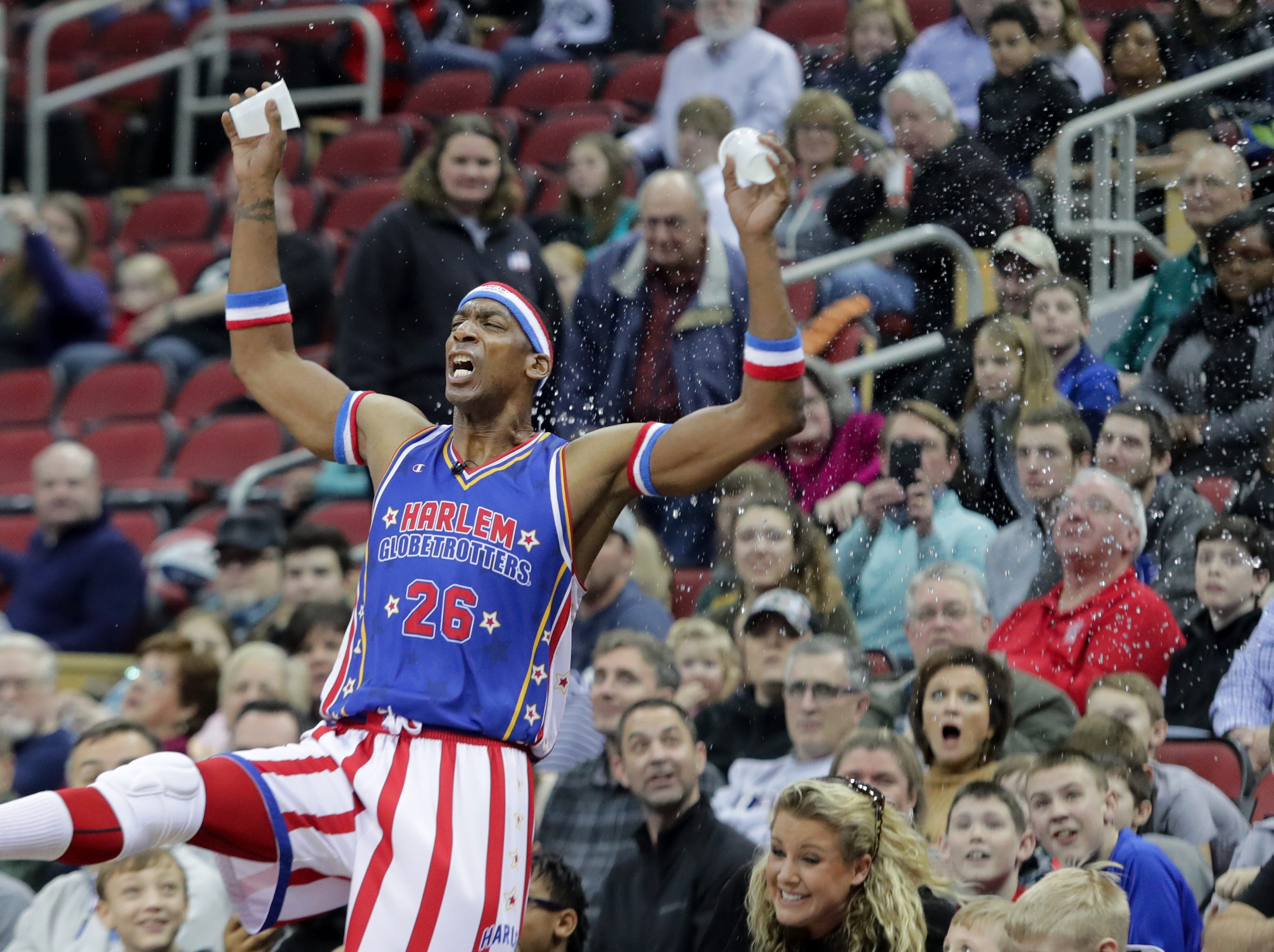 Harlem Globetrotters' Hi-Lite throws water on the crowd after a teammate missed a free throw.