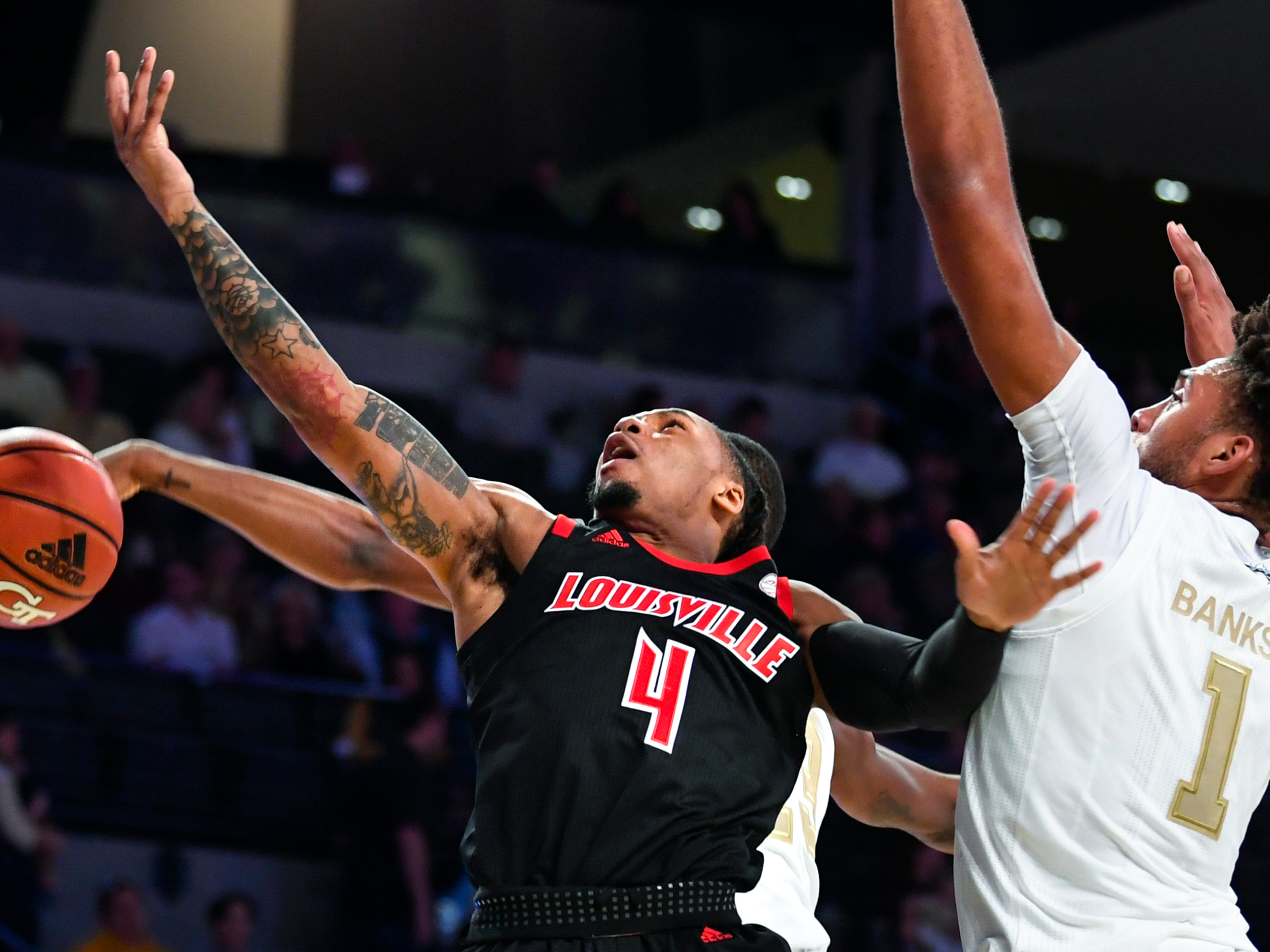 Louisville guard Khwan Fore (4) is stripped of the ball from behind by Georgia Tech guard Curtis Haywood II as forward James Banks III also defends during the first half of an NCAA college basketball game Saturday, Jan. 19, 2019, in Atlanta.