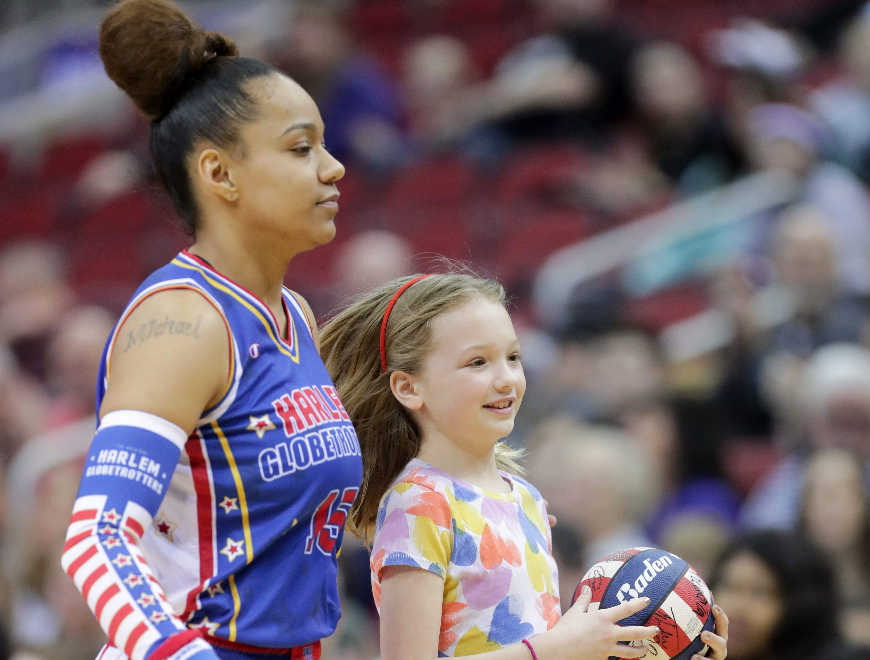 Harlem Globetrotters' Ice escorts a kid back to her seat after she won a prize. Jan. 19, 2019