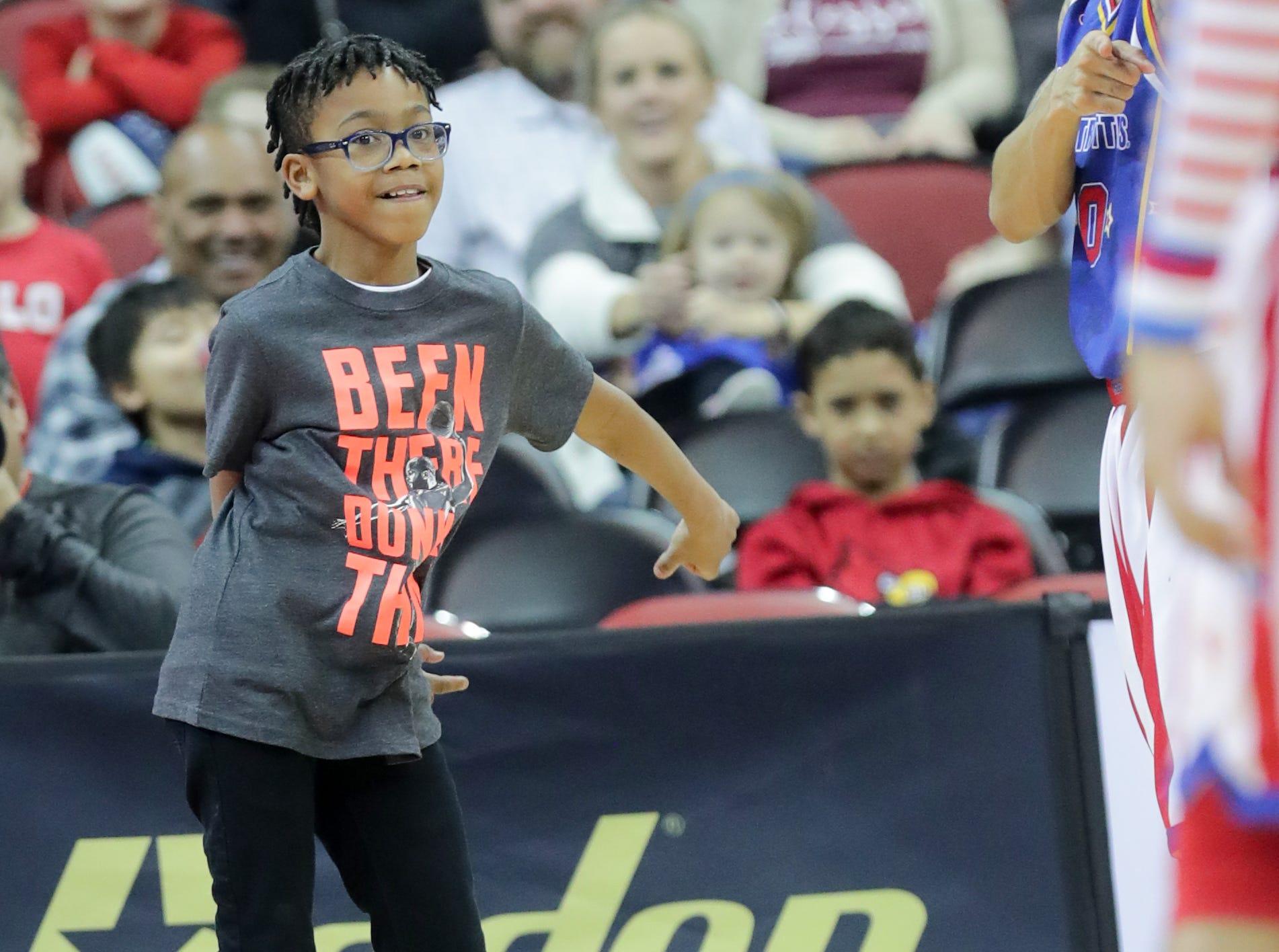 A kid shows the Harlem Globetrotters his celebration dance after making a basket. Jan. 19, 2019