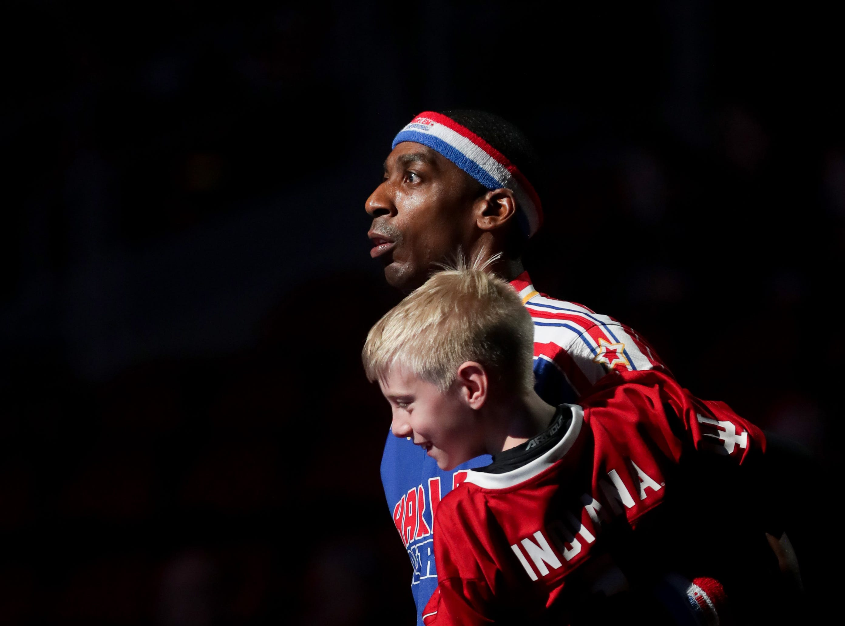 Harlem Globetrotters' Hi-Lite grabs a kid from the audience during player introductions.
