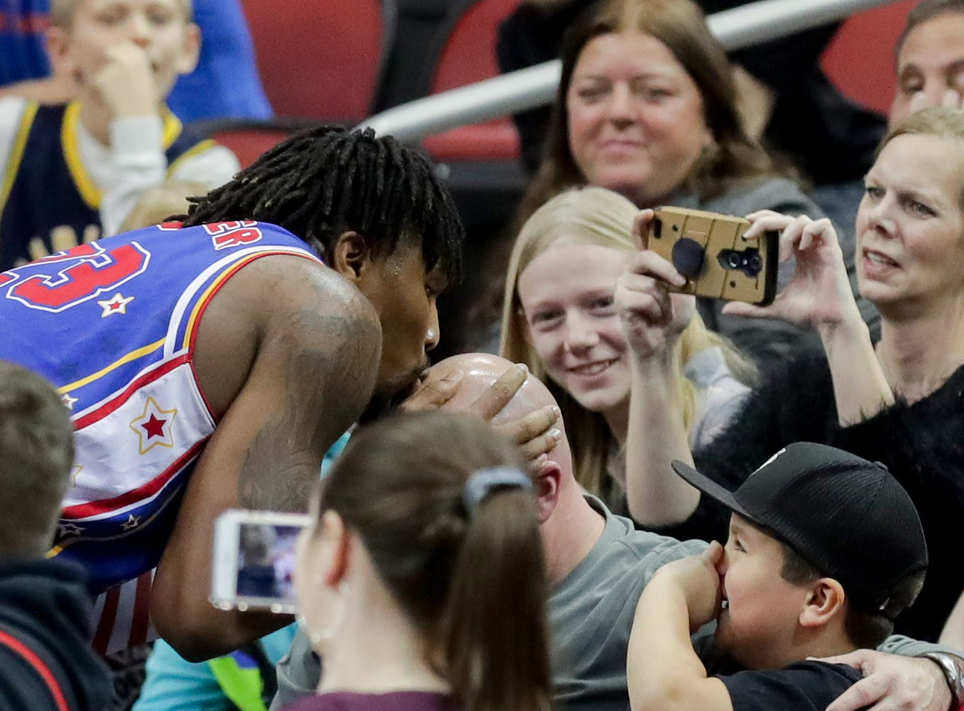 Harlem Globetrotters' Thunder kisses a bald head in the crowd.