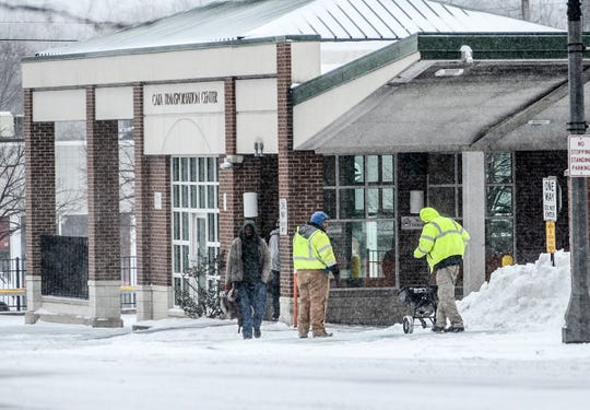 Workers at the CATA center in downtown Lansing spread salt on sidewalks Saturday in preparation for this week's historic winter blast.