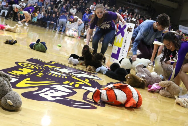 "Lexington students and fans threw stuffed toys onto the gym floor during the boys basketball game against Mt. Vernon on Friday, for the first ""Teddy Bear Toss."" Nearly 450 teddy bears were collected to support children in need."