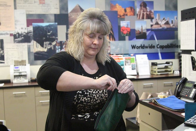 Karen Carter, a teller at Fahey Bank, runs customer account deposits Thursday. The bank is going through a dramatic change in leadership after the removal of its CEO and board of directors.