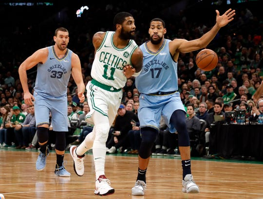 Boston Celtics' Kyrie Irving throws a behind-the-back pass past Memphis Grizzlies' Garrett Temple (17) during the first quarter of an NBA basketball game Friday, Jan. 18, 2019, in Boston. (AP Photo/Winslow Townson)