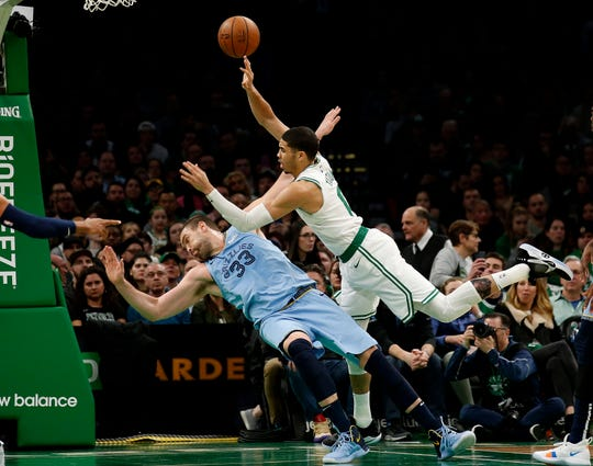 Boston Celtics' Jayson Tatum puts up a shot after running into Memphis Grizzlies' Marc Gasol during the second half of Boston's 122-116 win in an NBA basketball game Friday, Jan. 18, 2019, in Boston. (AP Photo/Winslow Townson)