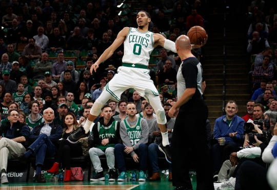 Boston Celtics' Jayson Tatum leaps to keep the ball in play during the first quarter of the team's NBA basketball game against the Memphis Grizzlies on Friday, Jan. 18, 2019, in Boston. (AP Photo/Winslow Townson)