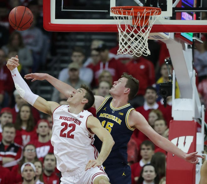 Wisconsin forward Ethan Happ and Michigan center Jon Teske compete for a rebound during the first half Saturday at the Kohl Center in Madison.