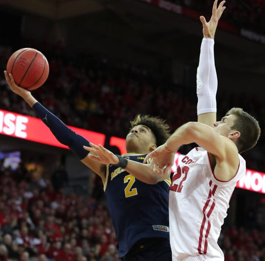 Ethan Happ defends Michigan guard Jordan Poole during the teams' first meeting this season.