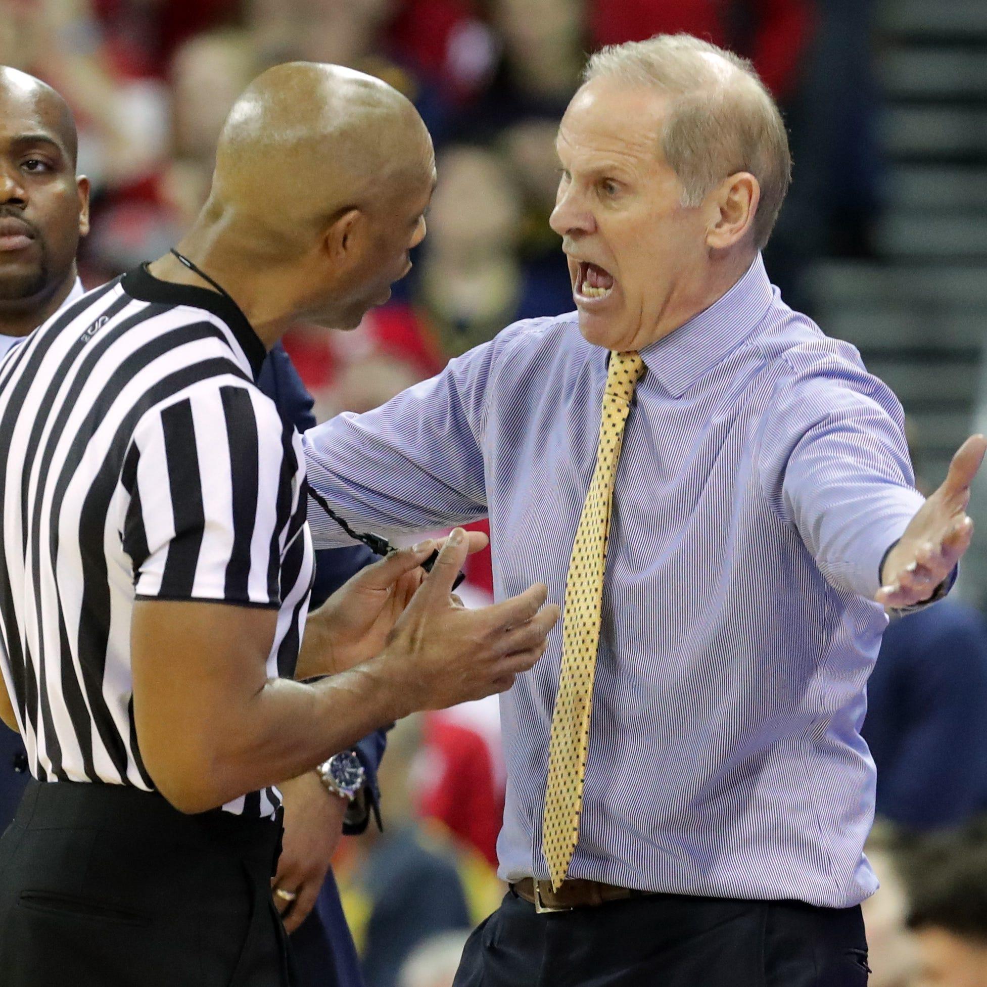 Michigan head coach John Beilein is beside...