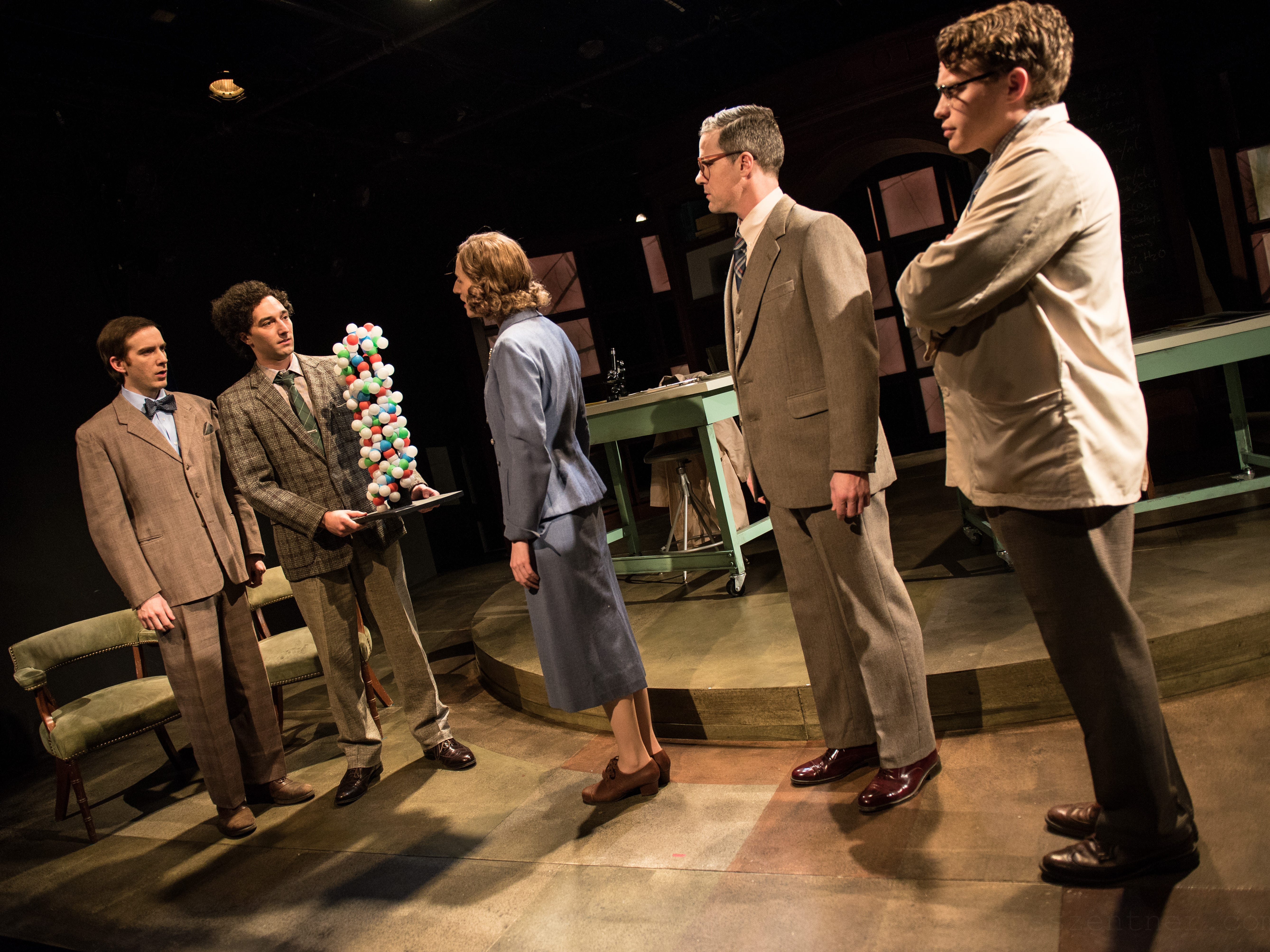 """Trevor Rees (left) and Nick Narcisi show a model of DNA to Cassandra Bissell, Neil Brookshire and Josh Krause in Renaissance Theaterworks' production of """"Photograph 51."""""""