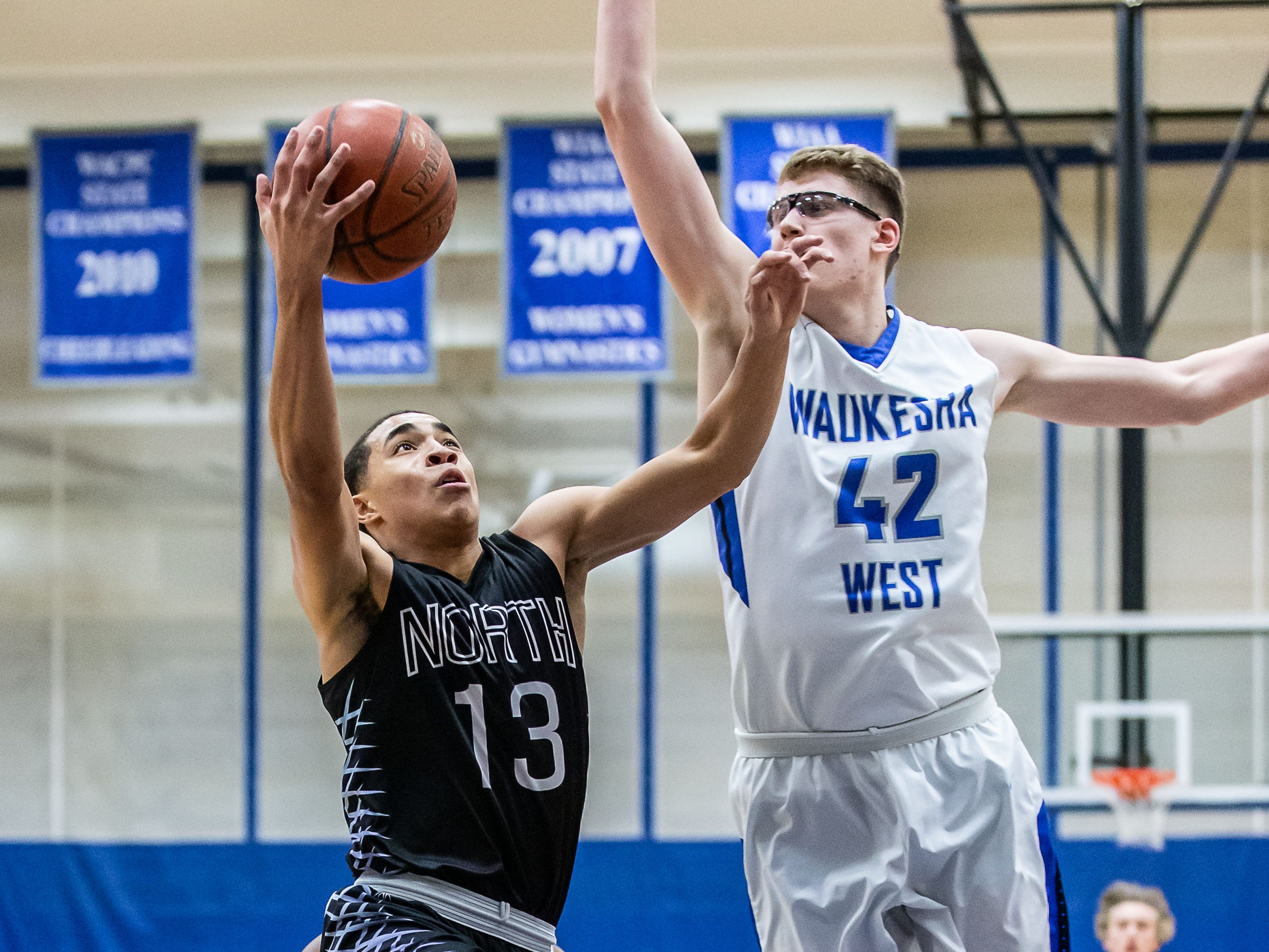 Waukesha West's David Skogman (42) prepares to swat away a shot by Waukesha North's Chimere Dike (13) during the game at West on Friday, Jan. 18, 2019.