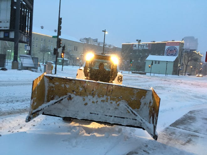 Streets and sidewalks were a slippery mess in downtown Milwaukee Saturday morning, but crews were clearing the way.
