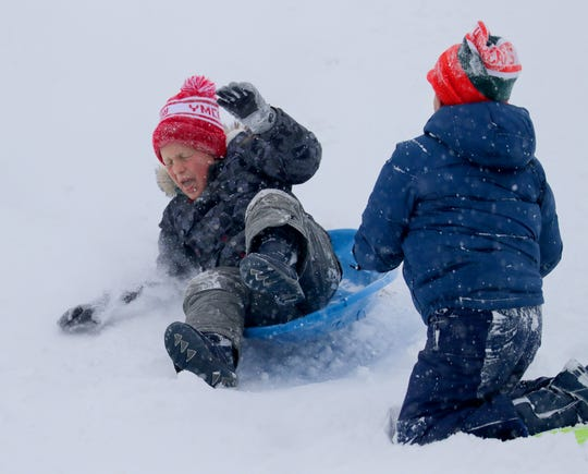 Jonah Allen, 6, avoids his brother, Jett, 8, both of Fox Point, while sledding on Mount Bayside hill in Bayside Saturday.