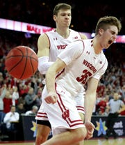 Wisconsin forwards Nate Reuvers (front) and Ethan Happ celebrate during the waning moments of the Badgers' upset victory over fourth-ranked Michigan on Saturday at the Kohl Center in Madison.