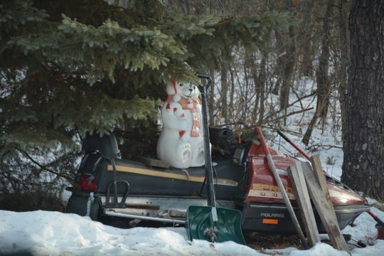 An old snowmobile and holiday decoration sit along the driveway of the Eau Claire Acres home in Gordon where Jayme Closs was allegedly held for months by Jake Patterson.