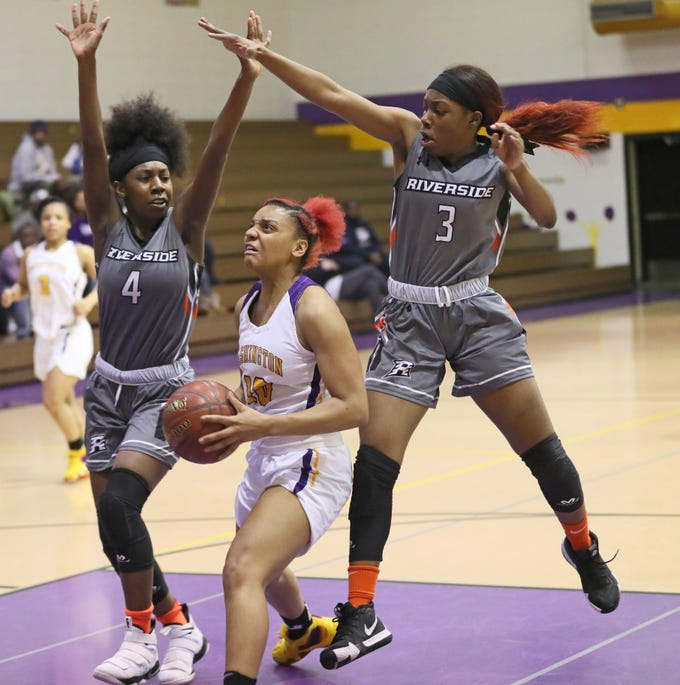 Washington's Lai'Janique Perry-Ellis splits Riverside defenders Sidney Scruggs (4) and Jaiden Claypool as she goes up for a shot on Friday night.