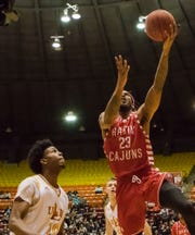 University of Louisiana at Lafayette's Jakeenan Gant (23) makes a lay-up while University of Louisiana at Monroe's Tyree White (10), unable to make a defensive play, watches during the game at Fant-Ewing Coliseum in Monroe, La. on Jan. 19.