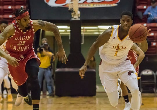University of Louisiana at Monroe's Travis Munnings (1) brings the ball back down court after making a steal against University of Louisiana at Lafayette's Jakeenan Gant (23) during the game at Fant-Ewing Coliseum in Monroe, La. on Jan. 19.