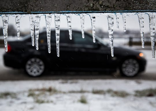 A car drives along a sleet-covered road.