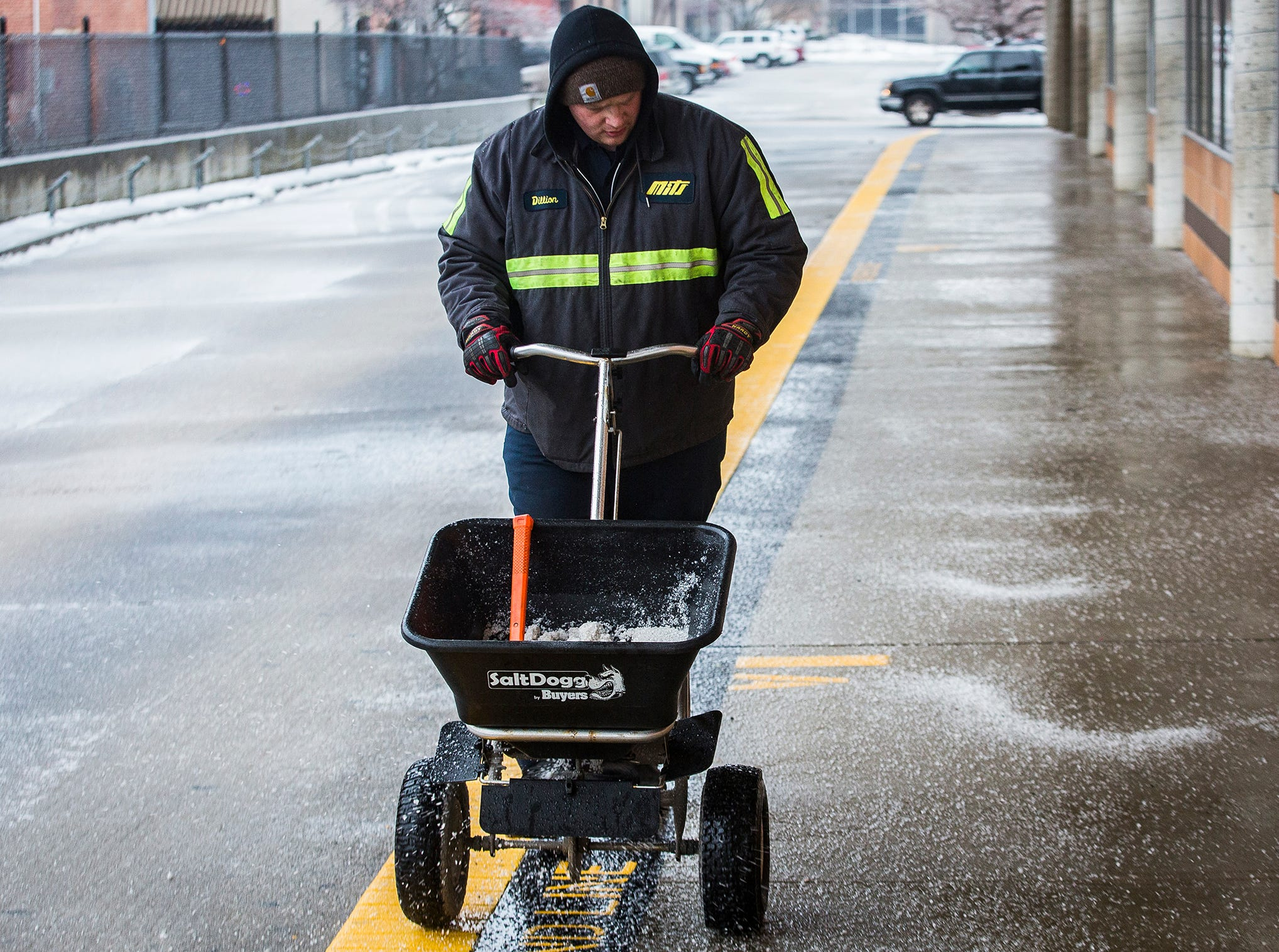 City workers spread salt at the Mits Station in downtown Muncie Saturday.