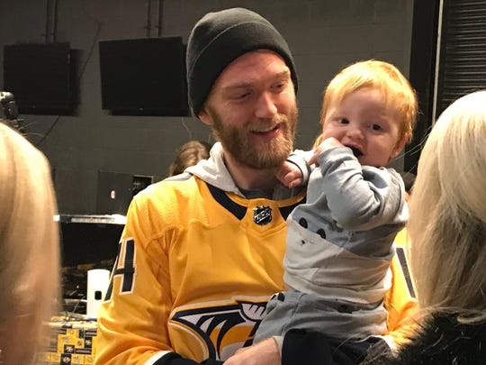 "Predators defenseman Mattias Ekholm holds his son William during the team's ""Hockey and Heels"" night at Bridgestone Arena on Wedesday, Jan. 16."