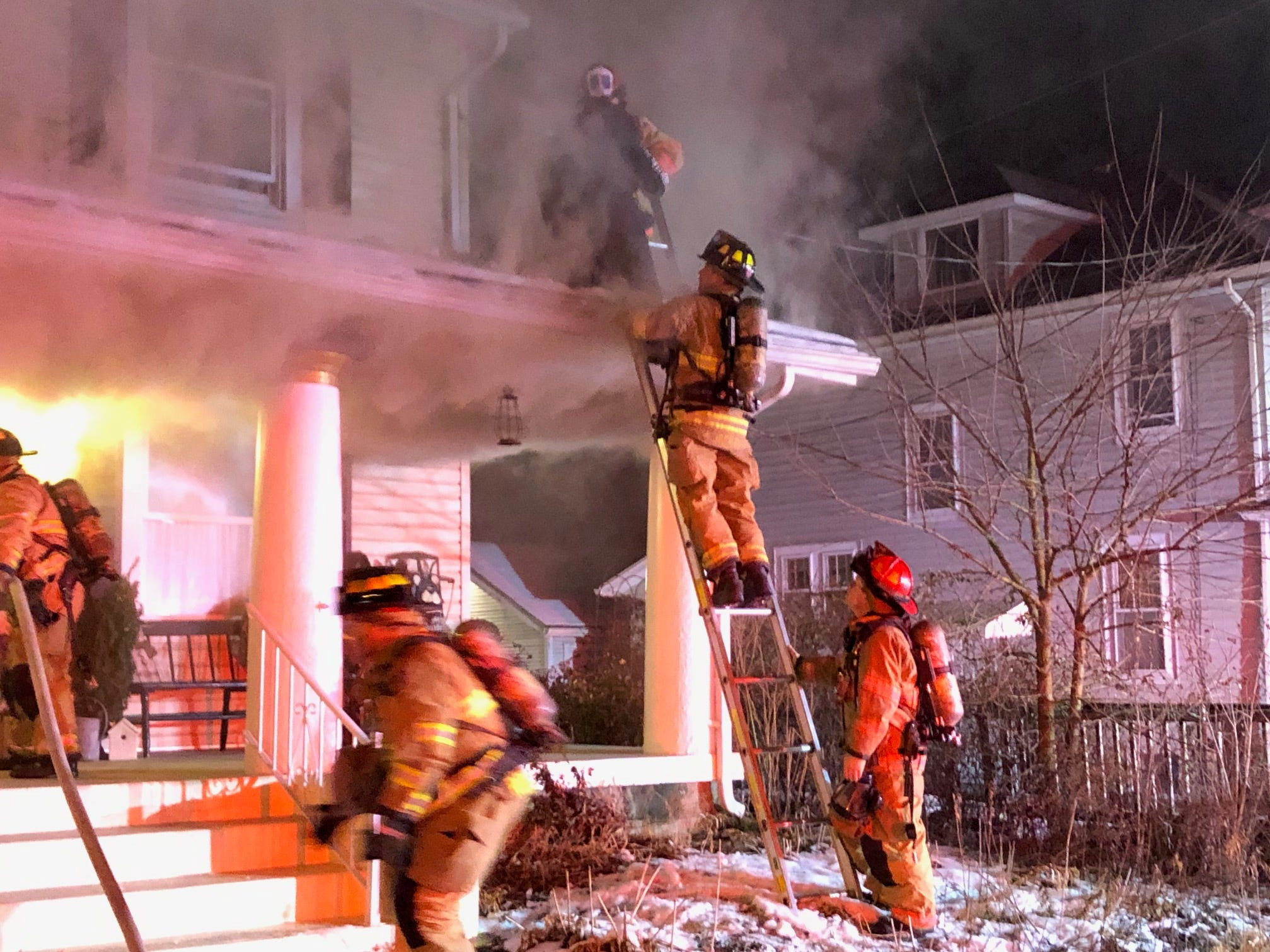 Firefighters help rescue a resident and a dog from a home on North 21st Street early Saturday morning.