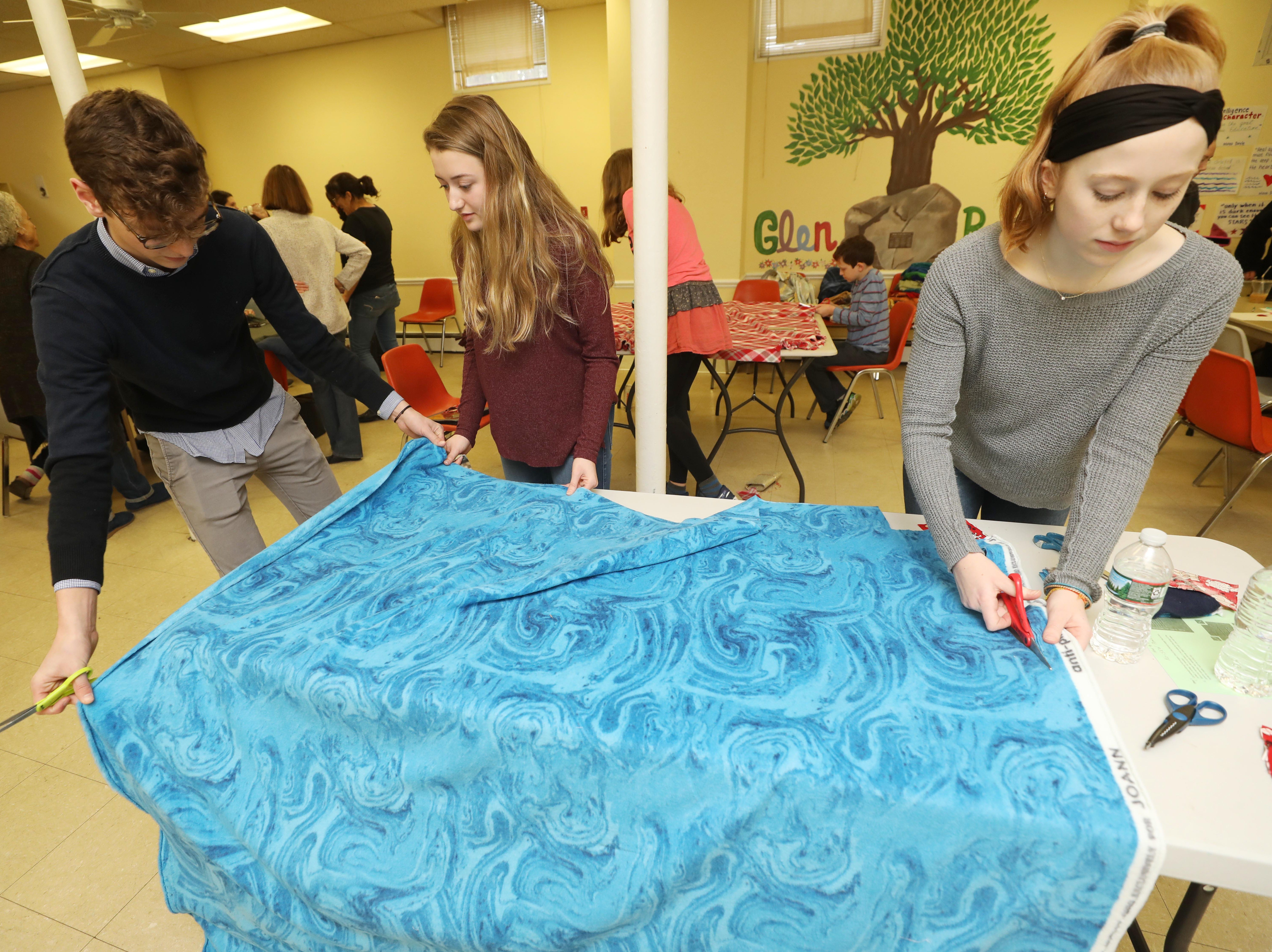 Matt Shiels, President of Blankets for Good, organizer of the event, Lauren Amram, a Glen Rock HS junior and Melinda Somers a junior at Glen Rock and Key Club board member work on making a blanket that will be given to those who are homeless inn New Jersey. It's part of a Day of Service at the Glen Rock Annex on January 19, 2019 in recognition of Martin Luther King Day.