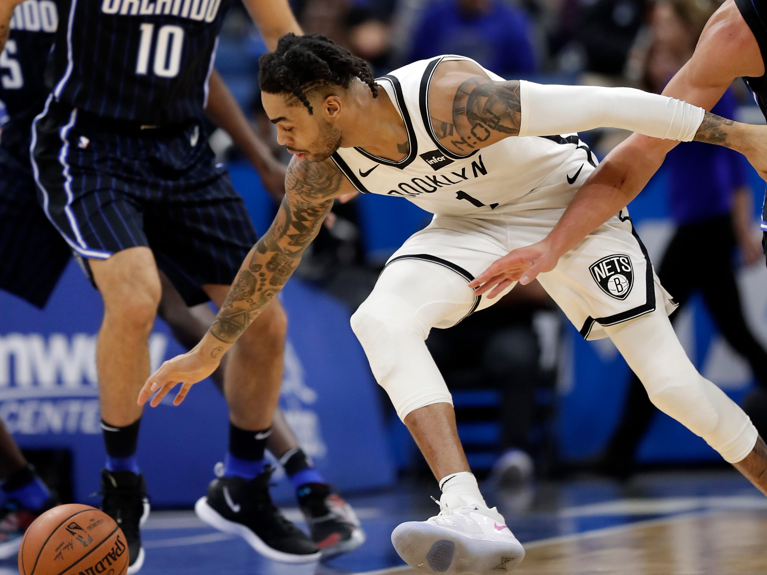 Brooklyn Nets' D'Angelo Russell, right, goes after a loose ball in front of Orlando Magic's Evan Fournier (10) during the first half of an NBA basketball game, Friday, Jan. 18, 2019, in Orlando, Fla.