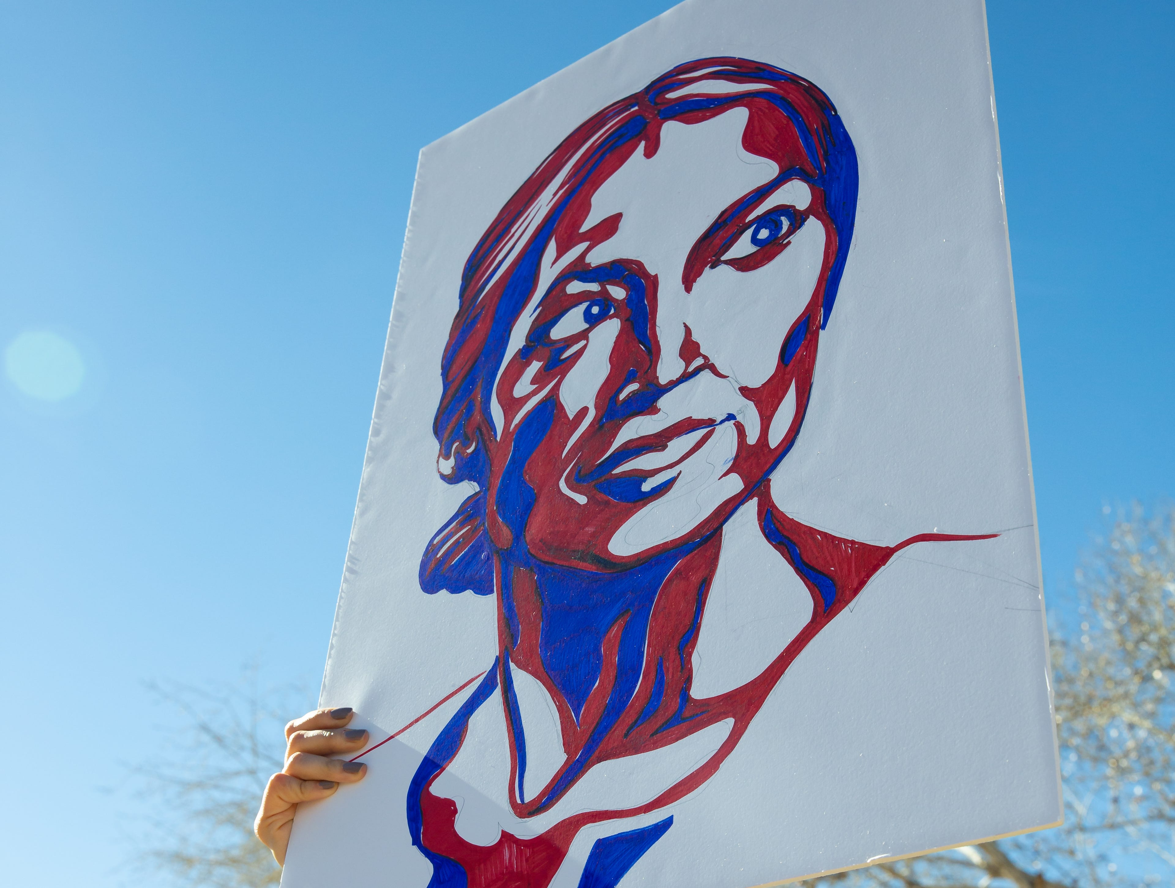 Raquel Madrigal hold a sign painted by Henry Hartig of Rep. Alexandria Ocasio-Cortez's, D-N.Y. on Saturday, January 19, 2019 at Albert Johnson Park during the 2019 Las Cruces Woman's Rally.