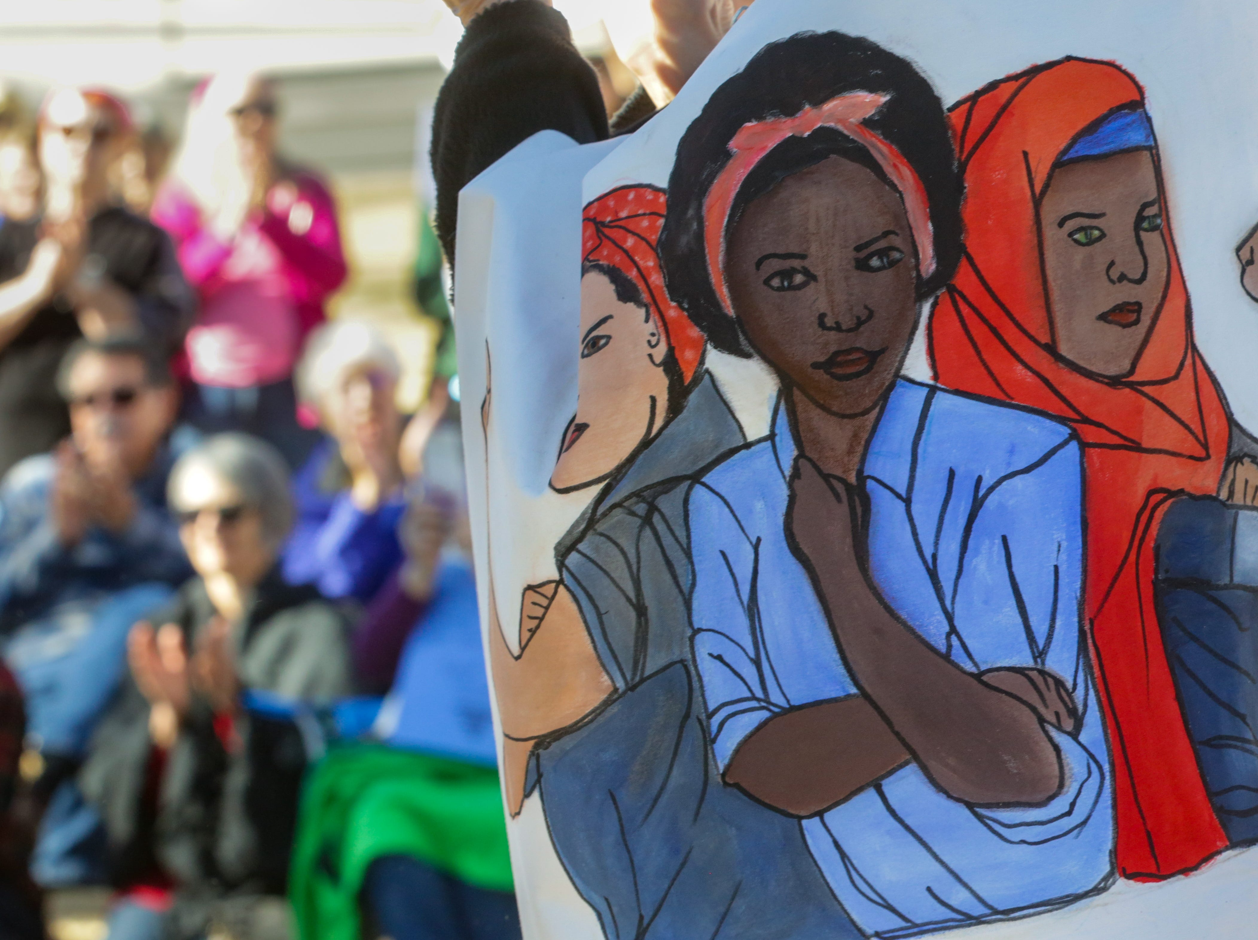 Eileen VanWie wears a banned with strong women depicted on it while the crowd is pictured on Saturday, January 19, 2019 at Albert Johnson Park during the 2019 Las Cruces Woman's Rally.