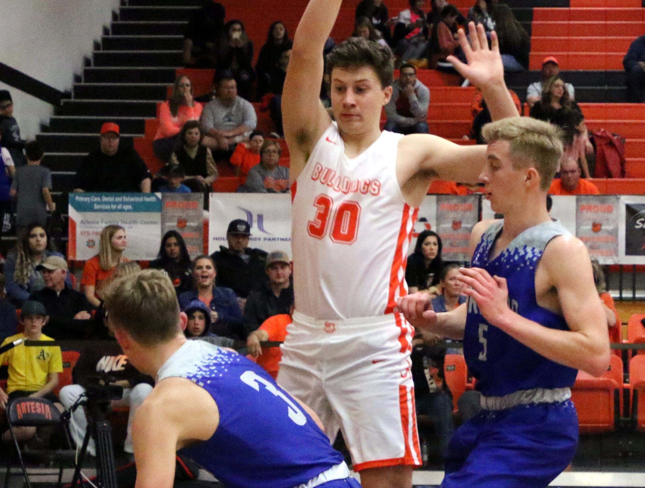 Artesia's Clay Houghtaling posts up to defends against a shot during Friday's game against Carlsbad.