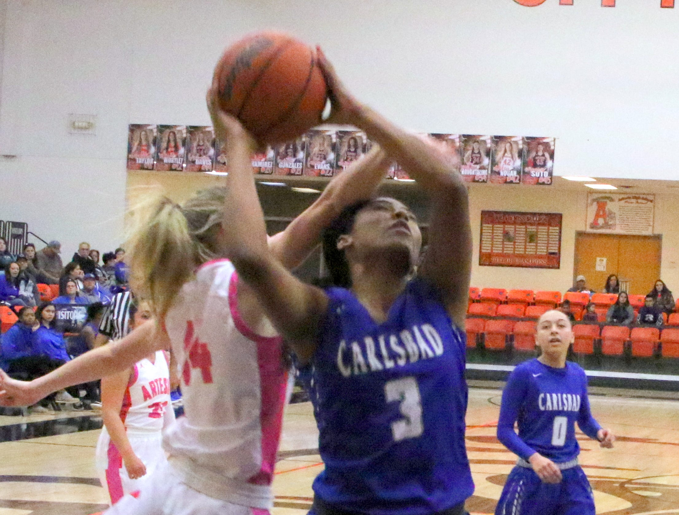 Carlsbad's Destiny Young (3) is fouled by Artesia's Brehnan Davis during Friday's game. Young finished with two points and Carlsbad swept the season series with a 58-35 win.